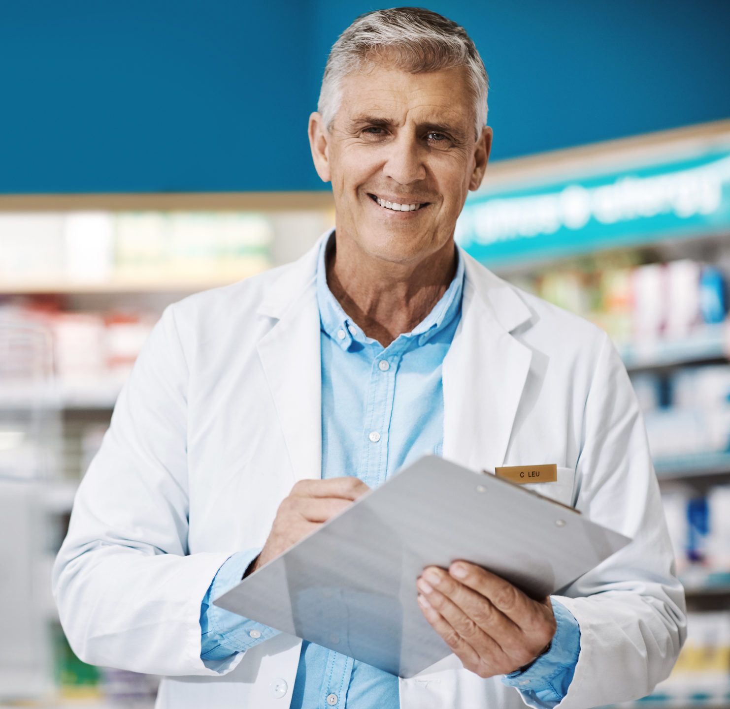 male pharmacist writing on a clipboard in a drugstore